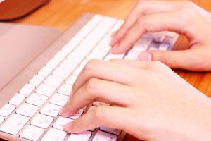 女性の手とキーボードの画像